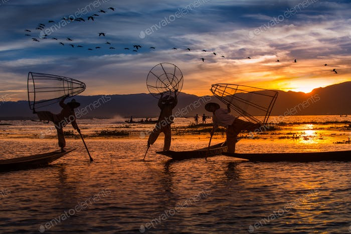Burmese Fishermen posing with conical nets at sunset, Inle Lake