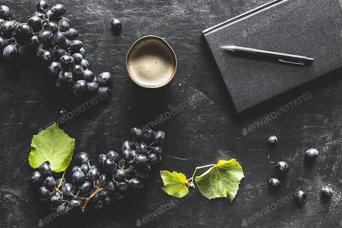 blue grapes on a dark background with a black notebook and a cup of coffee