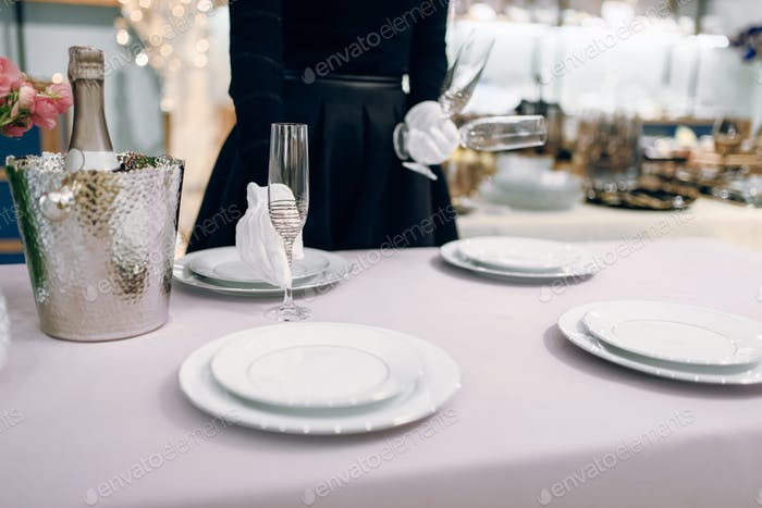 Waitress puts glasses for dining, table setting