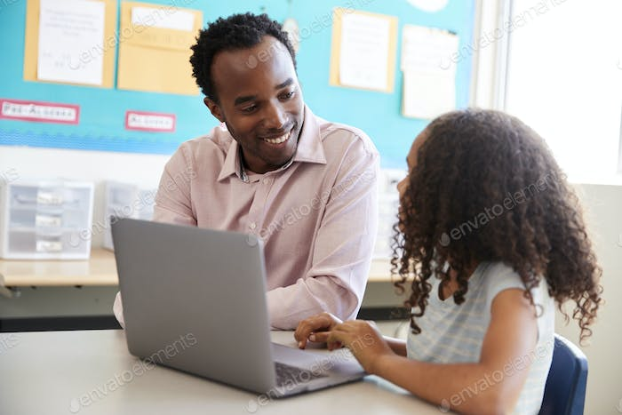 Teacher working with elementary school girl at laptop