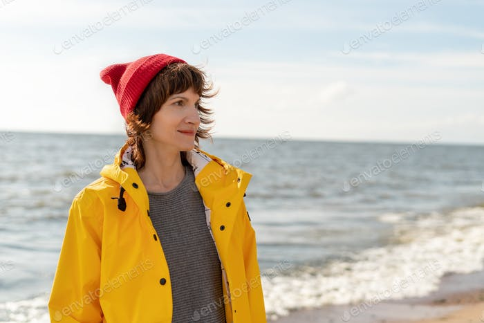 Waist portrait of mature woman in bright yellow cloak and red hat on shore