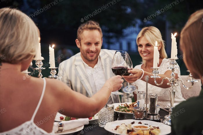 Knocking the glasses with wine. Group of friends in the elegant wear have luxury dinner