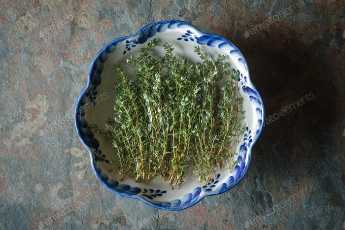 Green thyme in a bowl on slate close up