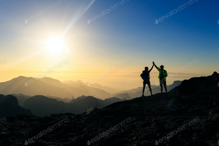 Couple hikers celebrating success concept in mountains