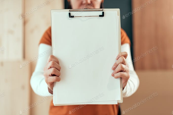 Female carpenter holding clipboard note pad paper mock up