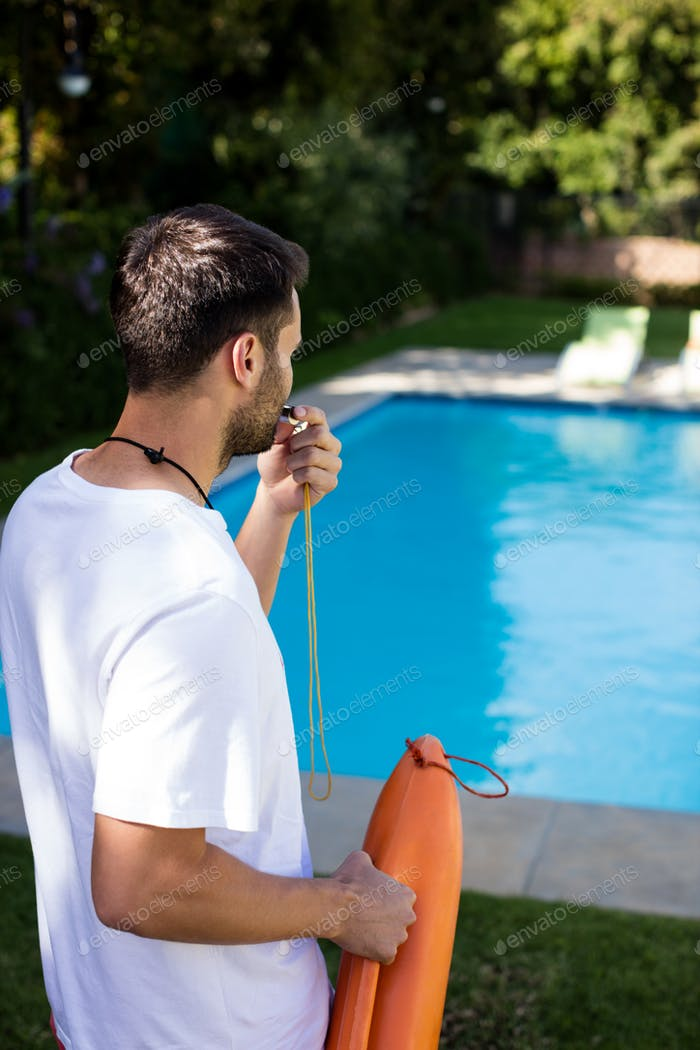 Lifeguard blowing whistle at poolside