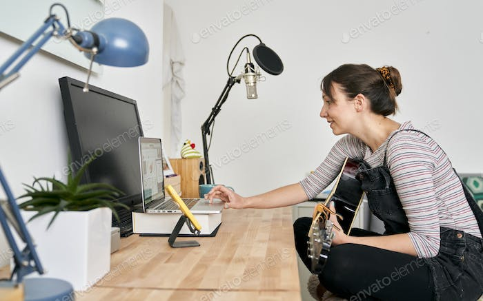 Woman using laptop for teaching guitar online