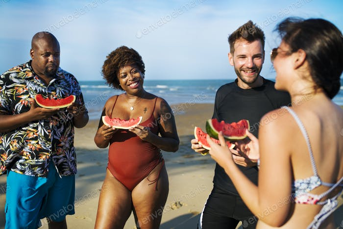Friends eating watermelon on the beach