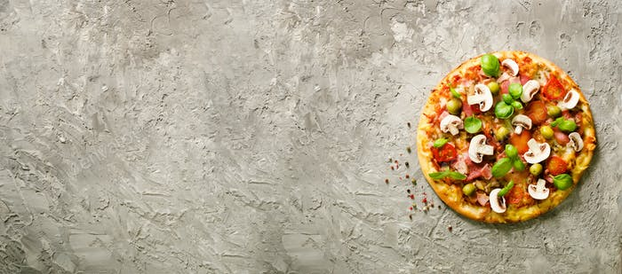 Fresh italian pizza with mushrooms, ham, tomatoes, cheese, olive, basil on grey concrete background