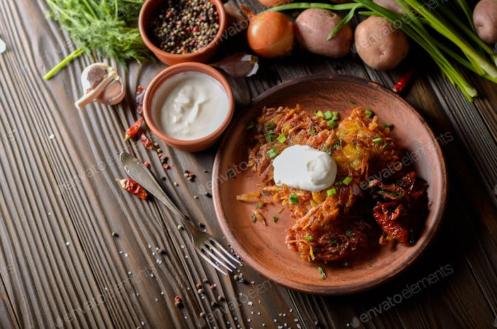 Top view at flat lay potato pancakes in clay dish with sun-dried