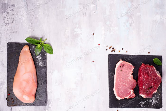 Different types of meat on dark slate cutting board. Lean proteins.