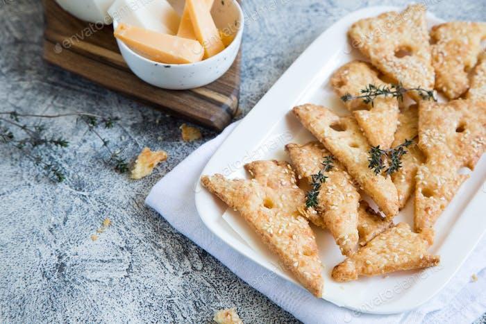 Hausgemachte Käse gebackene Kekse wie Käse auf einem weißen Teller und grauen Hintergrund
