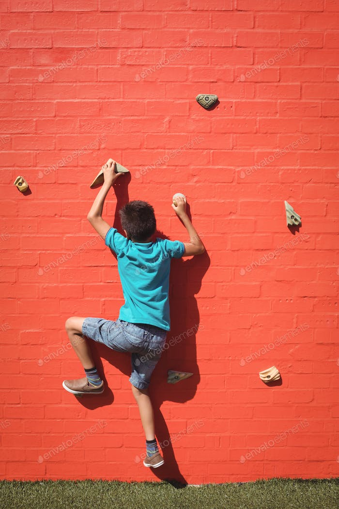 Boy climbing orange wall
