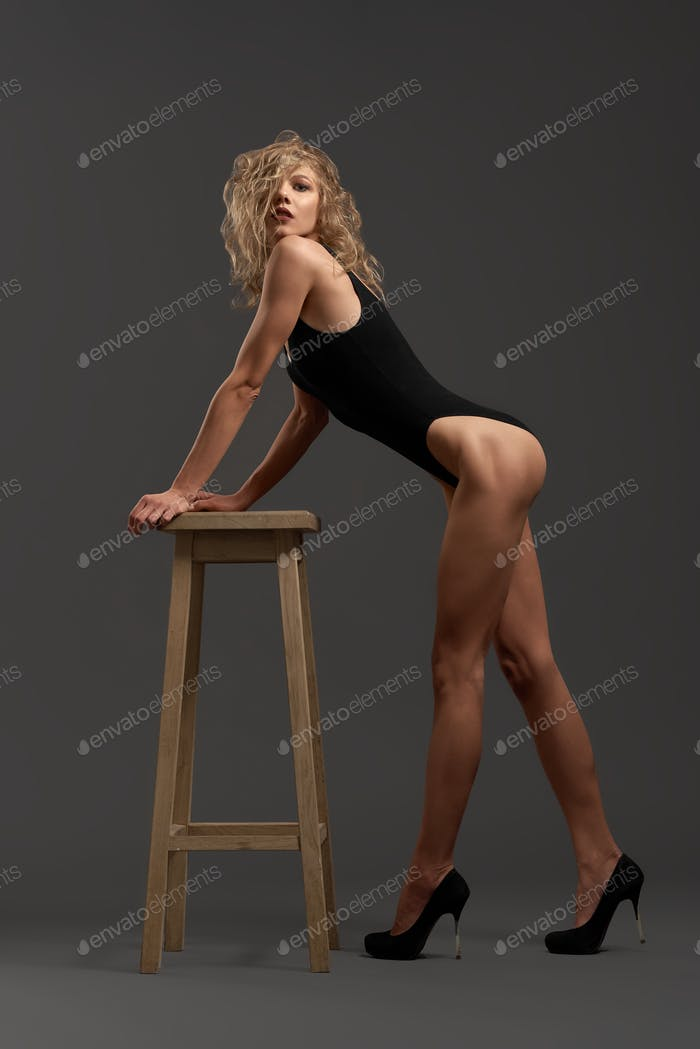 Blonde with curly hair, slender waist and long legs posing