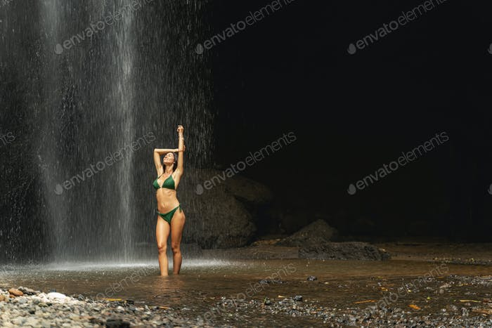 Real view of woman in swimsuit under waterfall
