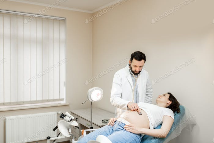 Doctor listening to a pregnant woman's belly