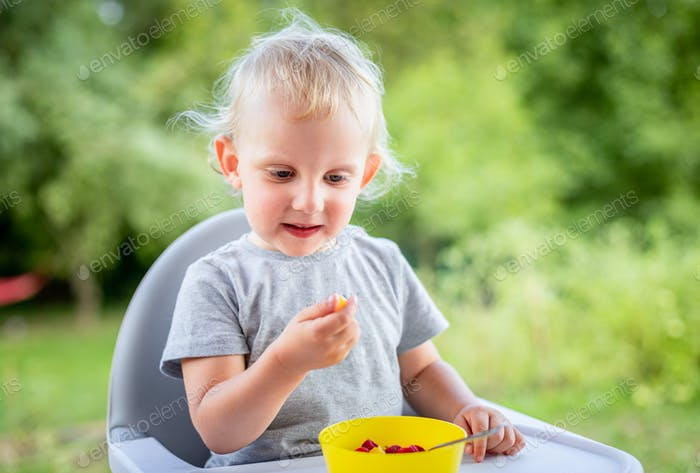 Cute happy baby boy eating outdoor and have fun
