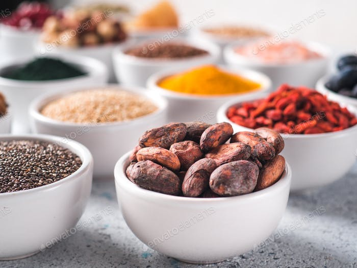 Raw cocoa bean in small white bowl and other superfoods