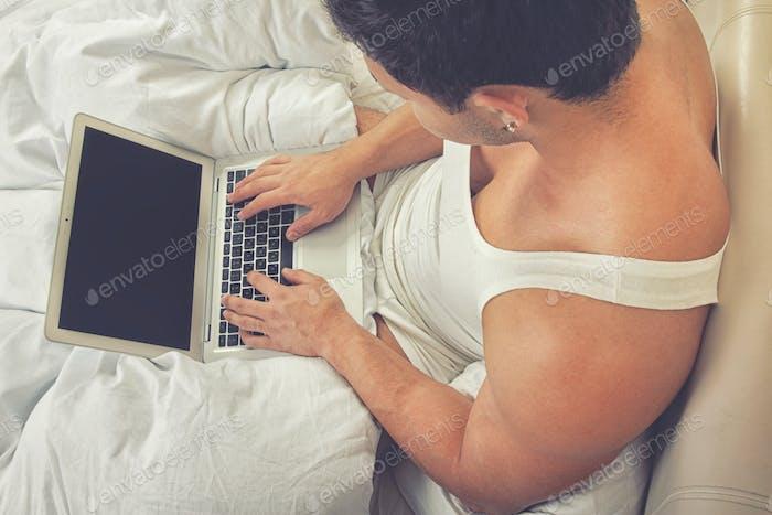 Человек, пользующийся ноутбуком, сидит на кровати
