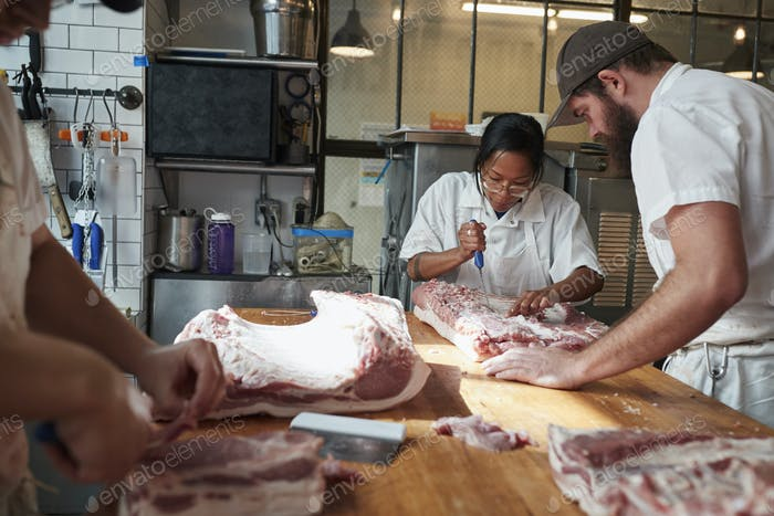 Three butchers preparing meat,cuts of meat to sell at a butcher's shop