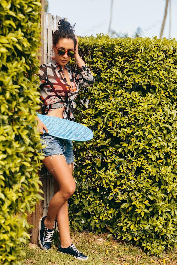 Hübsches Mädchen mit Skateboard vor grünem Zaun.