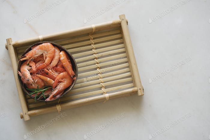 Shrimps with herbs in coconut bowl