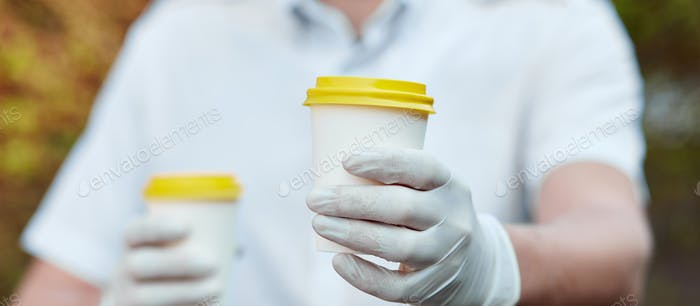 Delivery man in protective mask and gloves, takeaway cup of coffee