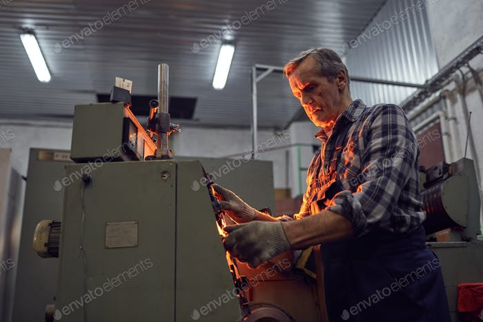 Engineer working on lathe