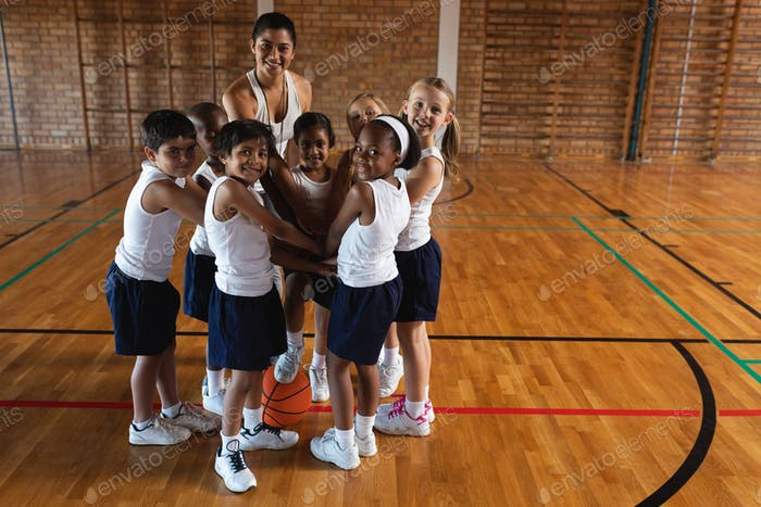 Schoolkids and female coach forming hand stack and looking at camera at basketball court in school