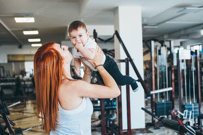 Junge Mutter mit ihrem jungen Sohn in der Turnhalle