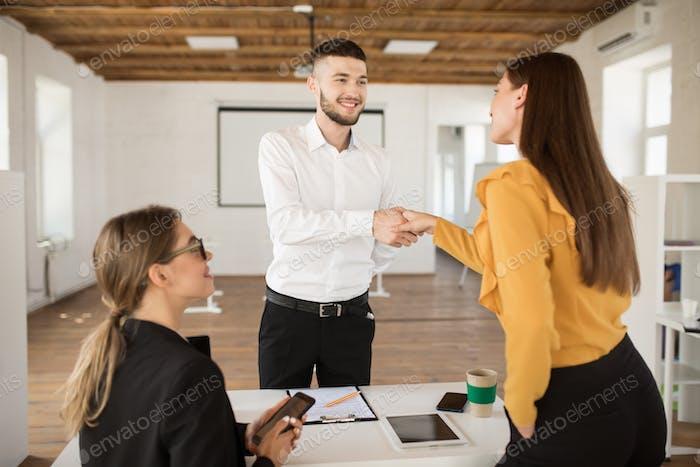 Улыбающийся мужчина заявитель счастливо пожимает руку работодателя. Молодой человек