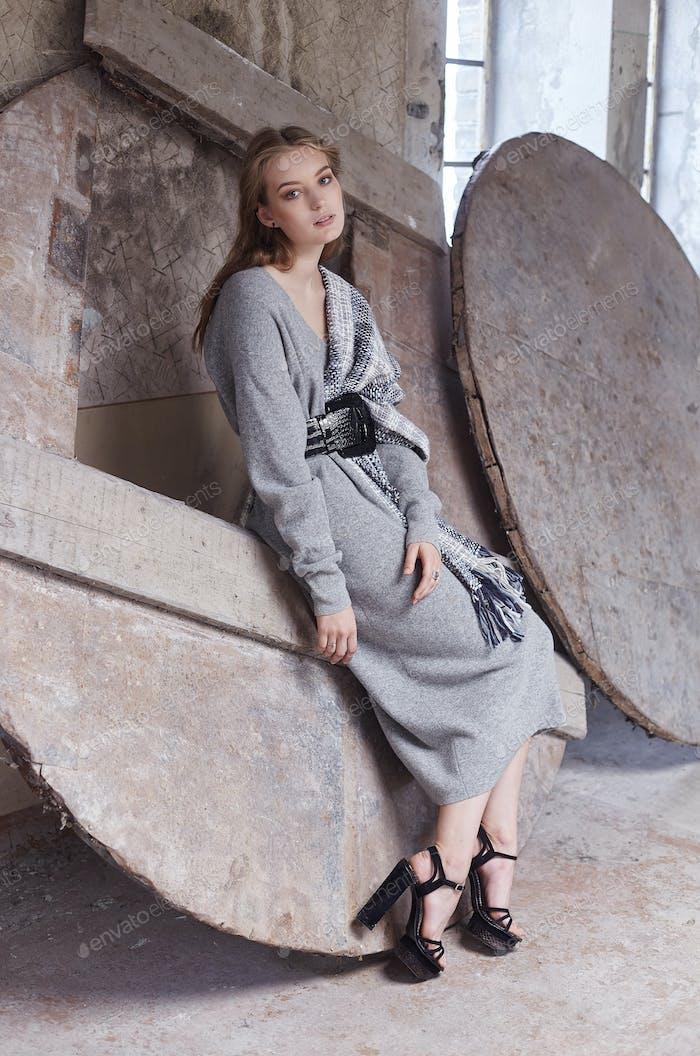 Slim woman in a long grey dress posing.