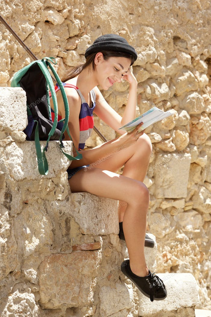 Young female traveler sitting outside reading map