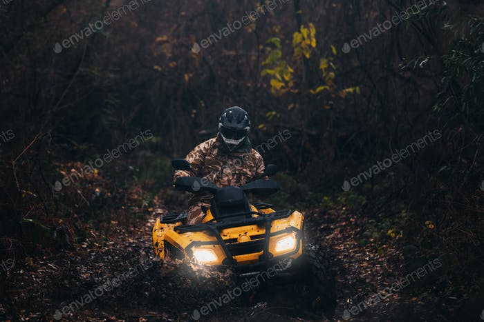 shot of quad bike rider driving in full protective equipment