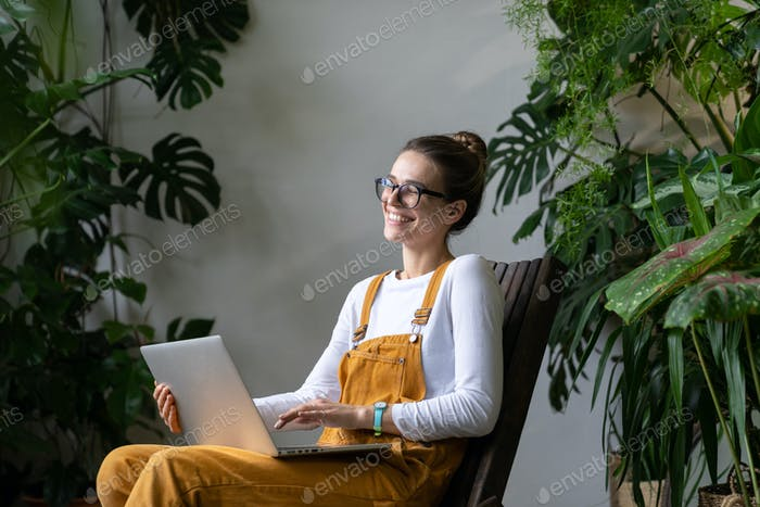 Lächelnde freiberufliche Frau schaut Webinar an, spricht im Video chat, Fernarbeit aus dem Hausgarten