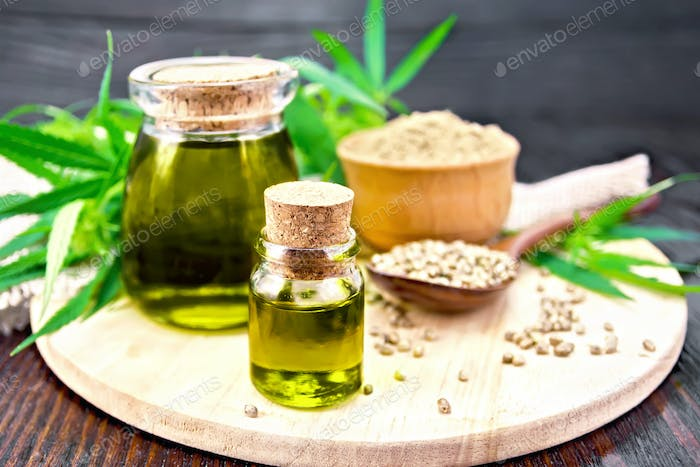 Oil hemp in two jars with flour on board