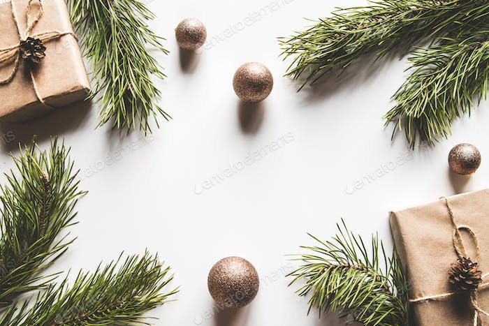 Gift box with christmas green framework and pine cones on white background. Copy space and Top view