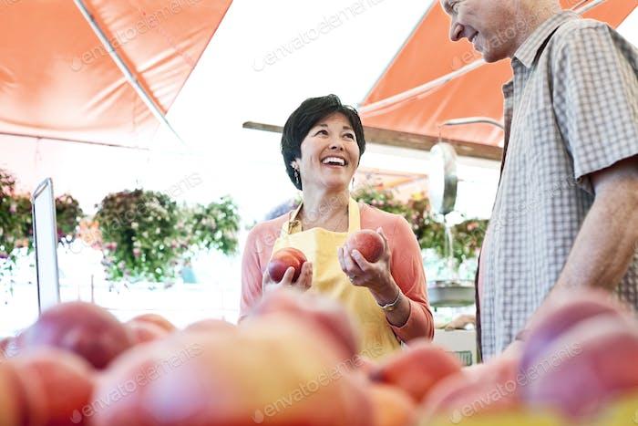 Lächelnde Frau trägt Schürze und Mann stehen am Stand mit frischen Pfirsichen an einem Obst und Gemüse