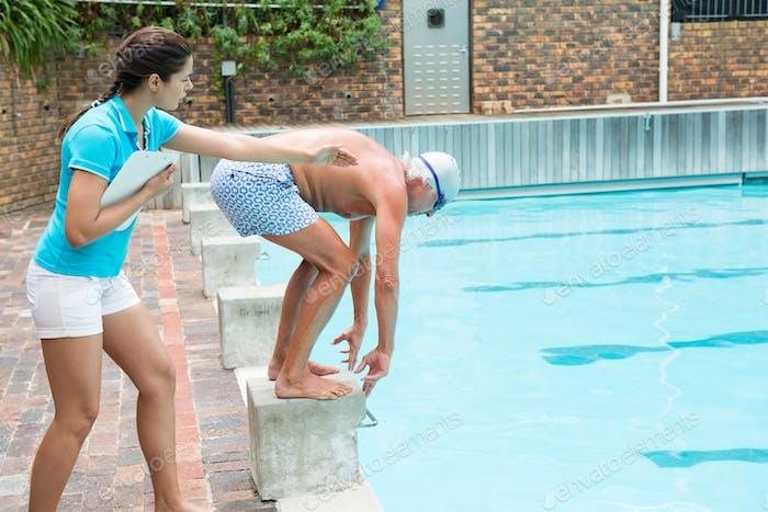 Swim coach assisting senior man in swimming
