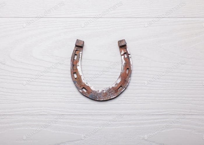 old rusty horseshoe on wooden white surface