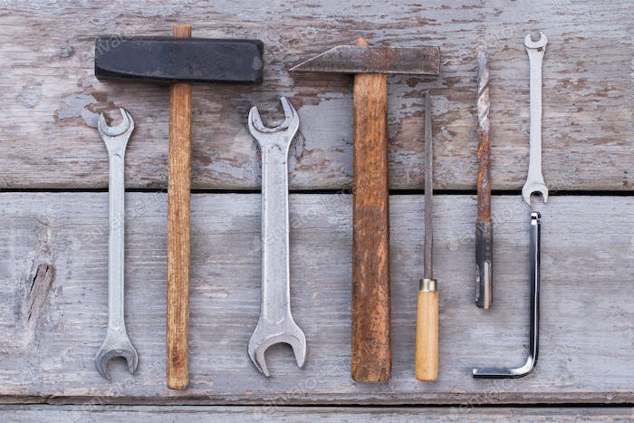 Set of old construction tools on wooden background.