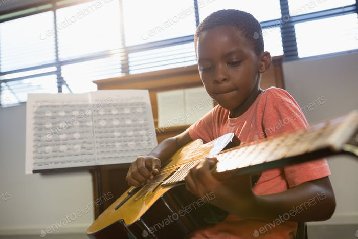 Boy playing guitar in class