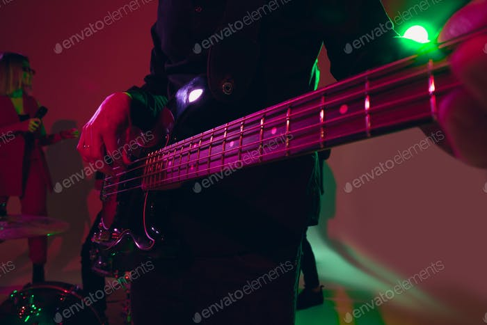 Young caucasian musician, band performing in neon light on red studio background