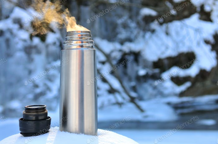Thermos with a hot drink on mountain waterfall