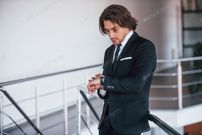 Checking time. Portrait of handsome young businessman in black suit and tie
