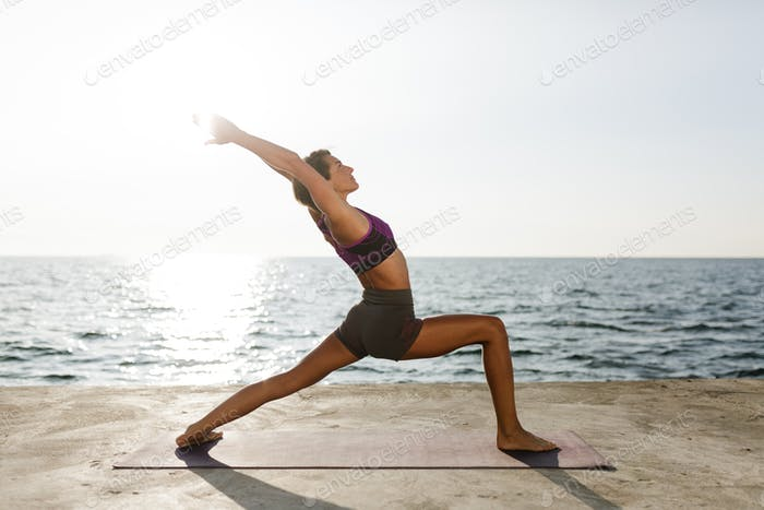 Pretty lady in sporty top and shorts practicing yoga with sea view on background