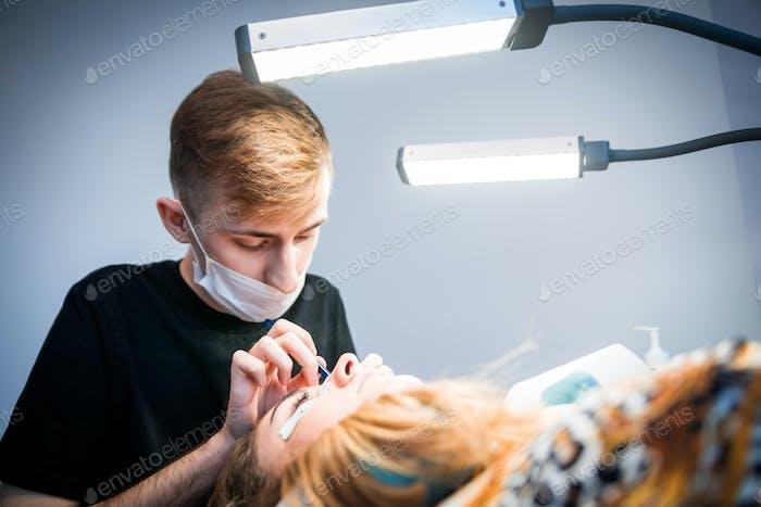 Мужской косметолог, применяющий наращивание ресниц в салоне красоты