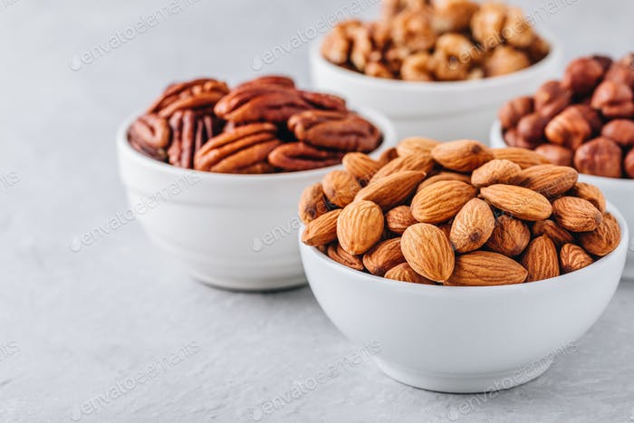 Almonds, pecans, walnuts and hazelnuts in white bowls on grey background. Nuts mix.