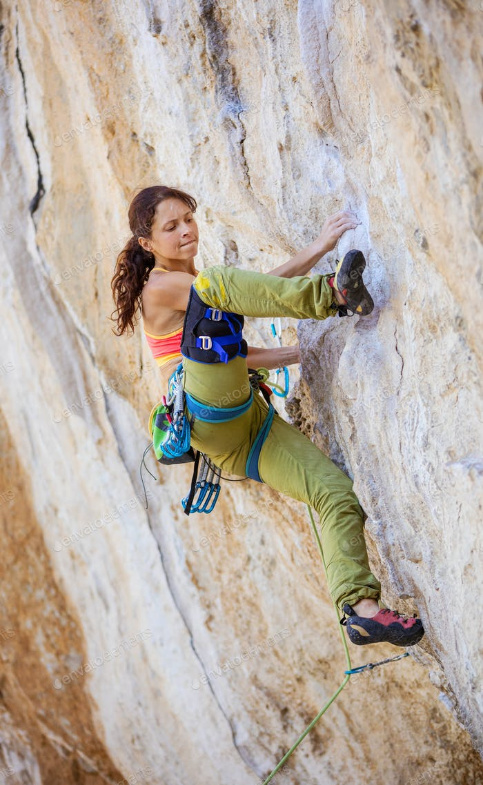 Female rock climber on challenging route on cliff