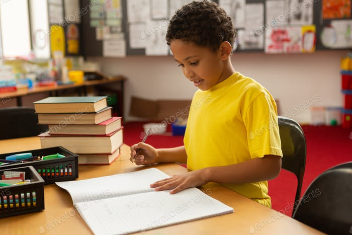 Side view of cute mixed-race schoolboy studying at desk in a classroom at elementary school